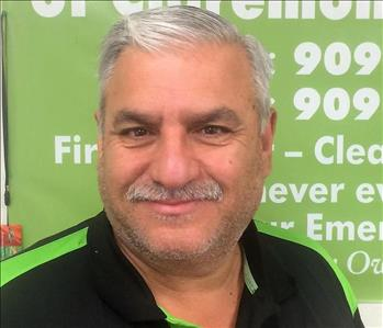 A seasoned gentleman with silver hair and mustache smiling in front of a SERVPRO banner.