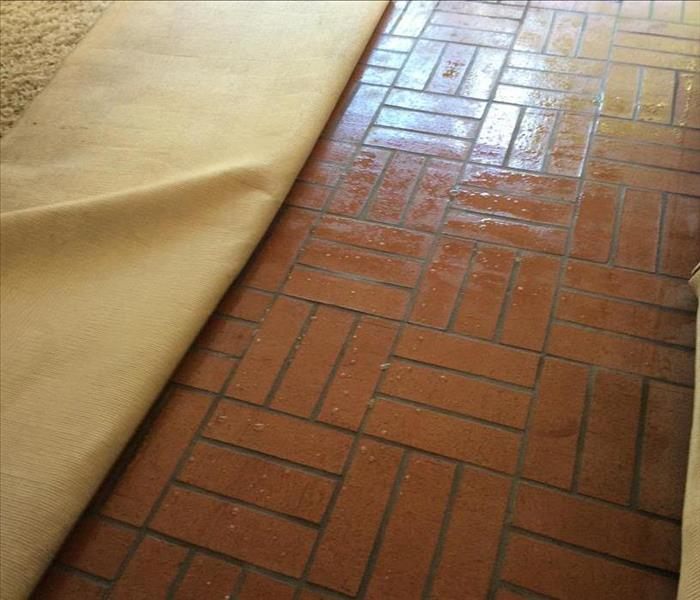 A beige carpet folded over, showing a red brick floor that is wet.