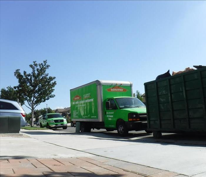 A green SERVPRO boxtruck and pickup truck parked in front of a wastebin.