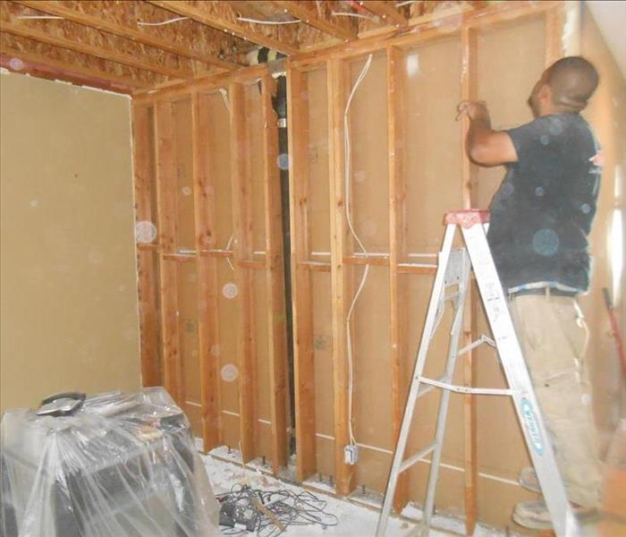 A technician inspecting a bare wall with clean studs that has been cleaned from fire damage.