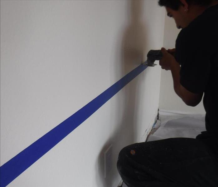 A SERVPRO of Claremont/Montclair technician carefully cutting drywall along a blue tape towards the bottom of the wall.