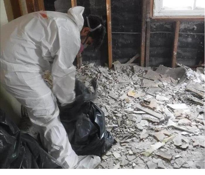 A technician dressed in a PPE suit cleaning up demoltion.